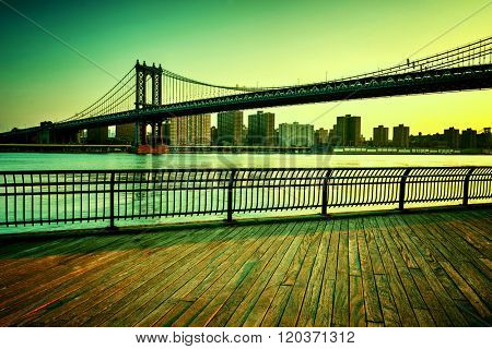 View of Manhattan Suspension Bridge Spanning the East River with View of Manhattan from Boardwalk in Waterfront Brooklyn Park, New York City, New York, USA, with Green Tint