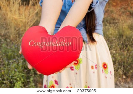 Women Hand Gently Hold Red Heart With Text Congratulation