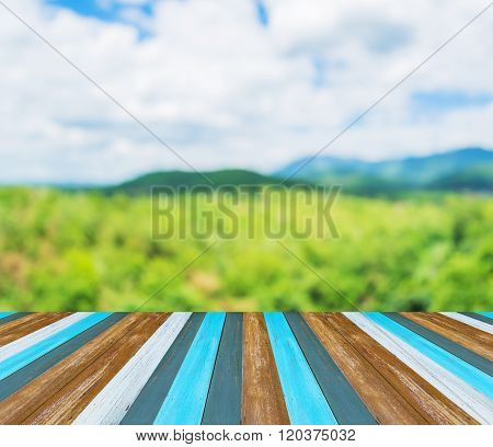 Wood Table And Blur Image Of Green Mountain In Background.