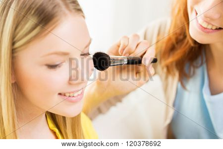 beauty, make up, cosmetics and people concept - close up of smiling young woman and visagist or friend with blush and makeup brush