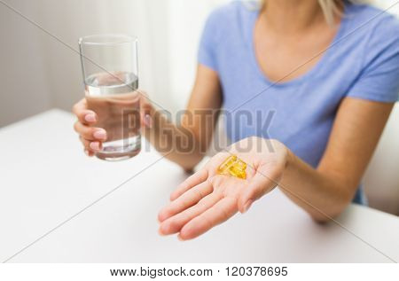 healthy eating, medicine, health care, food supplements and people concept - close up of woman hands holding pills or fish oil capsules and water glass at home