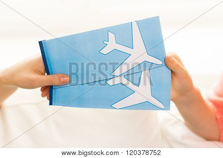 tourism, travel, vacation and people concept - close up of hands with airplane tickets at home