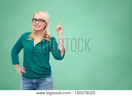 vision, optics, education, gesture and people concept - smiling young woman with eyeglasses pointing finger up over green school chalk board background