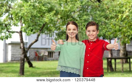 childhood, fashion, gesture and people concept - happy smiling boy and girl hugging and showing thumbs up over private house backyard background