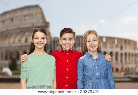 childhood, travel, tourism, friendship and people concept - happy smiling boy and girls hugging over coliseum in rome