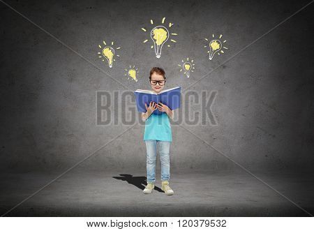 childhood, school, education, knowledge and people concept - happy little girl in eyeglasses reading book over concrete room background with light bulb symbol