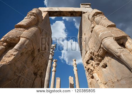 Lamassu Statues Of Persepolis Against Blue Sky With White Clouds In Shiraz