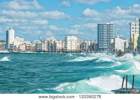 The Havana skyline with big sea waves crashing on the Malecon seawall