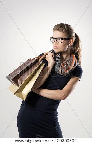 Portrait of female shopper with shopping bags posing in studio. Young attractive blond Caucasian woman model stylishly dressed looking at copy space.