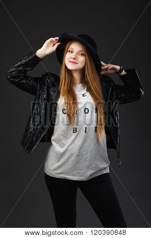 Portrait Of Beautiful Young Girl Wearing Black Hat And Leather Jacket In Front Of A Dark Gray Backgr