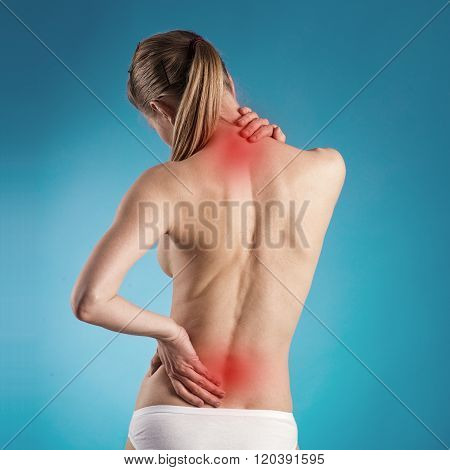 Woman suffering from lumbago or back pain. Young Caucasian female with osteoporosis indicated by red spots.