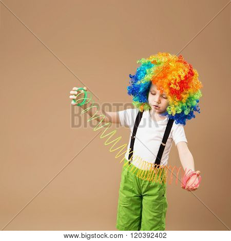 Little boy in clown wig smilling and playing with Magic Spring. Happy clown boy with large colorful wig. Birthday boy. Little clown boy with colorful hair and spring toy.