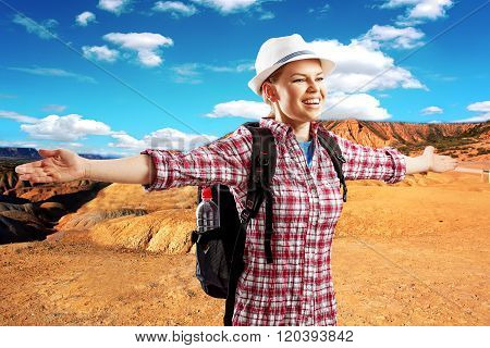 Happy woman climber enjoying desert view traveling with backpack.