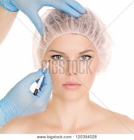 Plastic surgeon drawing lines over eyelid, isolated