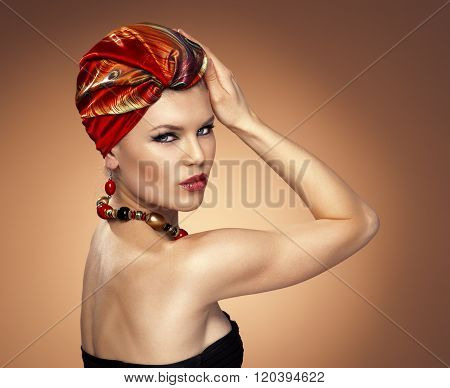 African style. Pretty glamour model with red turban in studio