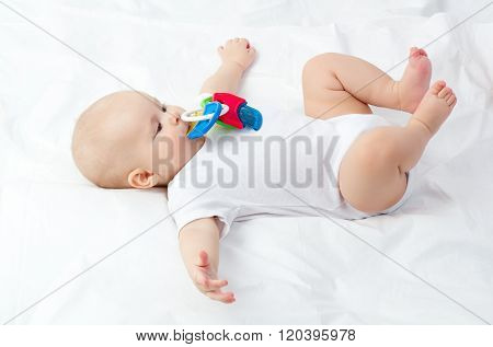 Cute small blond baby teething, lying on soft cover