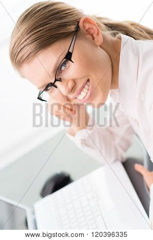 Smiling woman economist/ accountant sitting over keypad