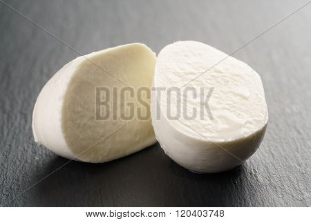 sliced mozarella ball on slate background
