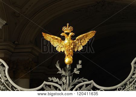 Golden Russian two-headed eagle on Hermitage gates. Fragment of beautiful ironwork fence.