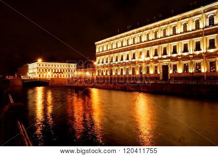 Night view of Griboyedov channel and historical classicism style building in Saint Petersburg.