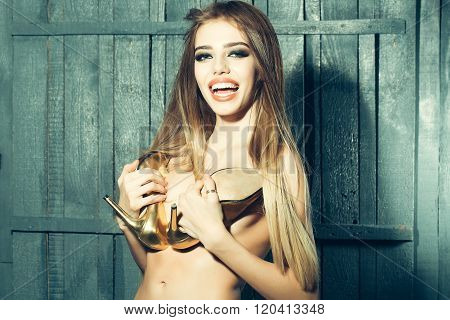 Sexy sensual smiling naked young woman with long windy hair style holding golden shoes covering bare chest on wooden background horizontal picture