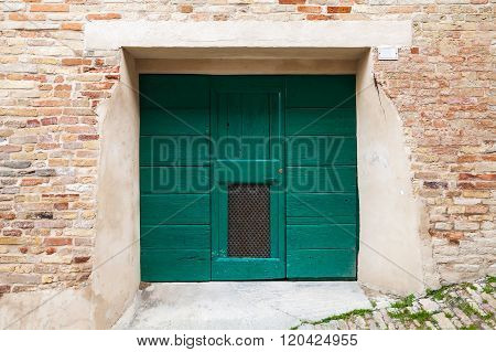 Green Wooden Gate In Old Brick Wal
