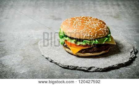 Fresh Burger With Cheese And Meat On A Stone Stand.