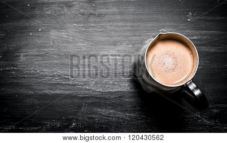 Pitcher Of Hot Chocolate. On Black Rustic Background.