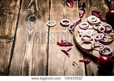 Onion Rings With Seeds On A Wooden Board.
