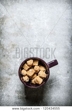 Mug With Dark Cane Sugar. On Stone Background.