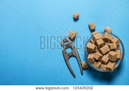 Cane Sugar Refined With Pliers. On Blue Table.