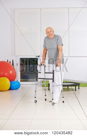 Smiling old senior man with walker in physiotherapy