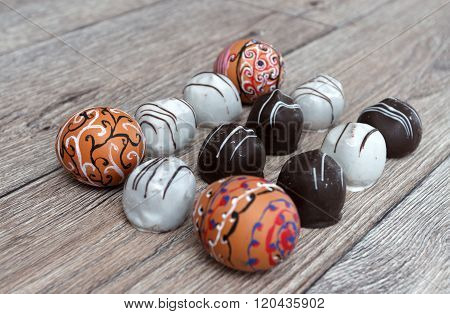 Handmade Colorful Painted Easter Eggs With Chocolate Candies  Against Wooden Background