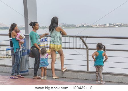 Group Of Women With Children Watching The River At Boardwalk