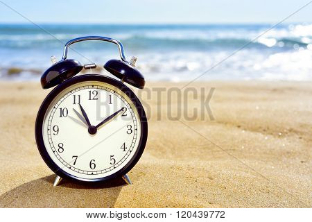 closeup of an alarm clock on the sand of a beach adjusting forward one hour at the beginning of the summer time
