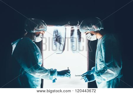 Two surgeons working and concentrating at operating table