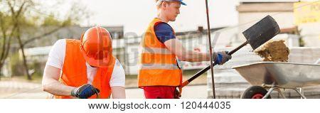 Workmen Pouring Sand Into Wheelbarrow