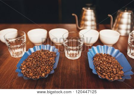 Roasted coffee beans with cups ready for a tasting