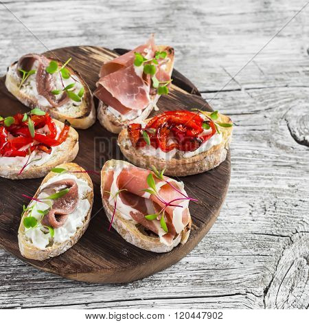Sandwiches With Goat Cheese, Anchovies, Roasted Peppers, Ham On A Wooden Rustic Board. Delicious Sna