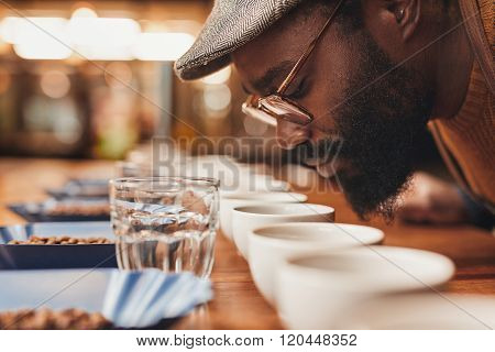 African man enjoying the aroma of fresh coffee at tasting