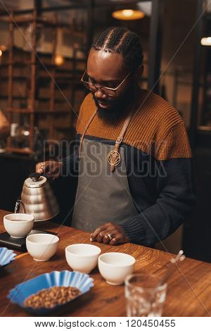 African barista pouring coffee in a modern roastery
