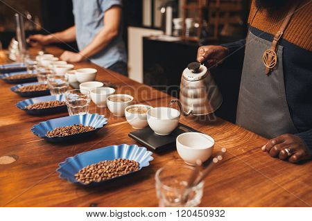 People with variety of coffee beans and cups at roastery