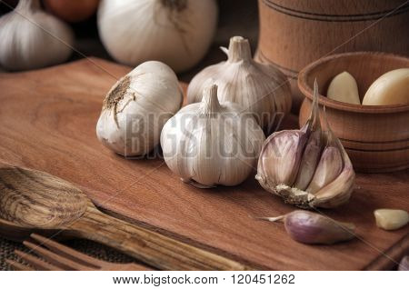 Garlic On Cutting Board , Close-up On Sacking. Burlap Background