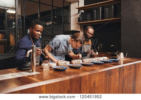 Baristas training in a modern roastery with varieties of coffee
