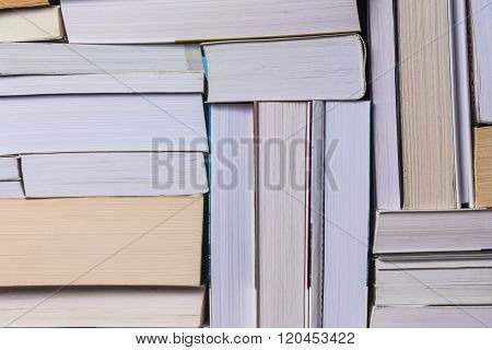 Stack of used old books on bookshelf
