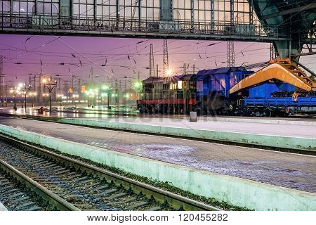 Train with industrial equipment at the railway station at night. Train with crane at the station in