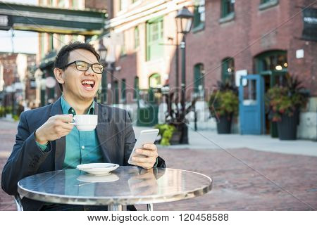 Laughing young asian man sitting in outdoor cafe with mobile phone holding cup of coffee enjoying success