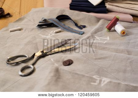 Composition of needle and thread with other sewing tailoring tools. Spool of thread, scissors, buttons,sewing supplies. Close up of scissor, buttons, thread and thimble on fabrics.