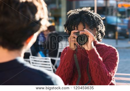 Young beautiful african woman taking photos of her boyfriend. Attractive young black girl taking a picture with a digital camera. Portrait of a woman photographer clicking a photo to remember.