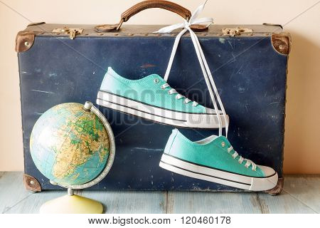 Travel concept with holiday suitcase, shoes and globe
